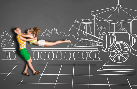 Happy valentines love story concept of a romantic couple against amusement park chalk drawings background. Male catching his girlfriend launched as a human cannonball.