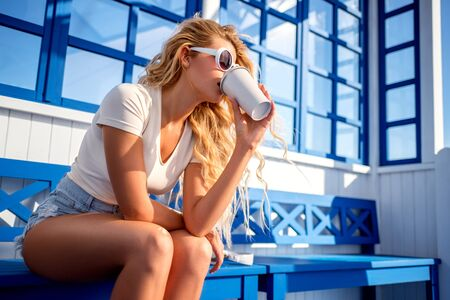 Beautiful young woman with take away coffee cup and music headphones near her, sitting on the bench and waiting for a water taxi.