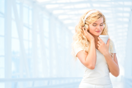 long: Beautiful young woman wearing music headphones, standing on the bridge with a take away coffee cup and posing against urban background. Stock Photo