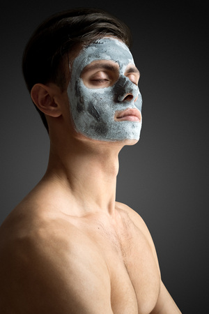 salon: Portrait of a beautiful young man with a facial clay mask, face and body skin care treatment. Stock Photo