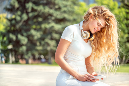 Beautiful young woman with music headphones around her neck, surfing internet on a smartphone and sitting against park background. Stock Photo