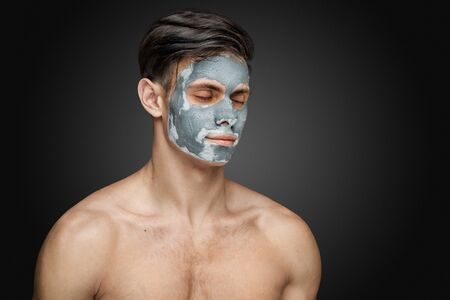 renew.: Portrait of a beautiful young man with a facial clay mask, face and body skin care treatment. Stock Photo
