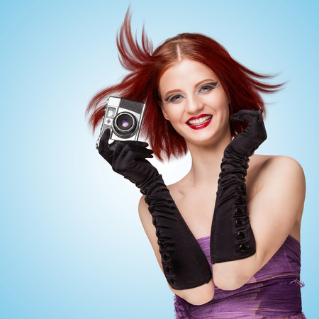 Glamorous smiling girl, wearing long gloves, holding an old vintage photo camera, and saying cheese on blue background.