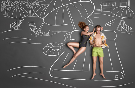 woman lying in bed: Love story concept of a romantic couple lying on an air mattress against chalk drawings background. Male listening to the music in the headphones and reading a book, female trying to gain his attention.
