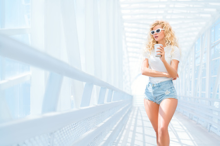 Thoughtful blonde young woman in sunglasses with take away coffee cup posing on the urban bridge. 版權商用圖片 - 77011278