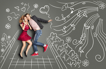 Happy valentines love story concept of a romantic couple walking in the park, sharing headphones and listening to the music against chalk drawings background. Stock Photo
