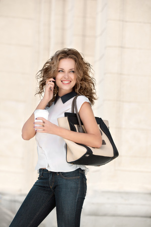 A beautiful businesswoman with the phone holding a cup of take away coffee.