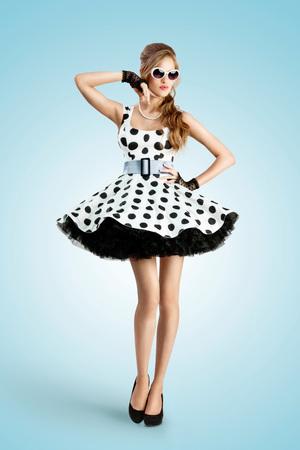 Una foto de la vendimia de una hermosa chica pin-up que llevaba un vestido y gafas de sol retro del lunar.