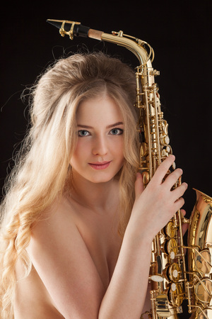 adult sex: Portrait of a sexy beautiful nude pin-up girl from 60s or 70s, posing with a gold jazz saxophone and smiling on black background.