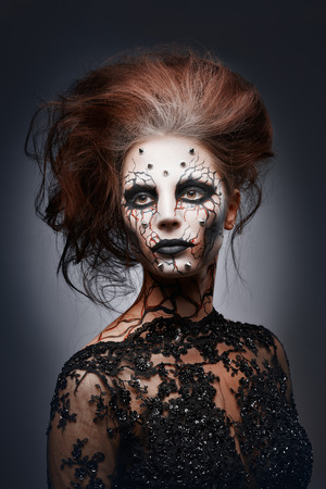 A girl posing in a creepy halloween costume of a witch with peircing and cracked painted face.