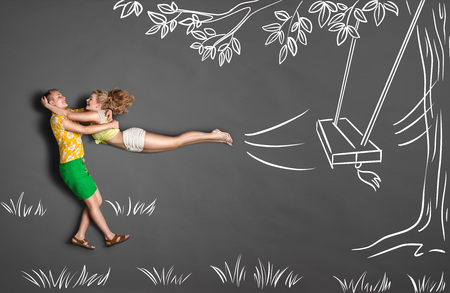 Happy valentines love story concept of a romantic couple against chalk drawings background. Male catching his girlfriend jumping from tree swings. Imagens