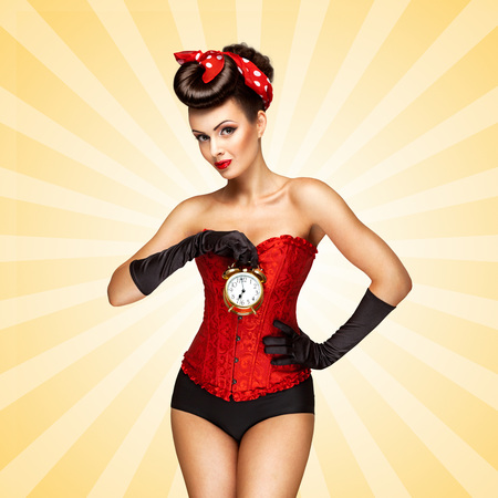 Glamorous pinup girl in a red vintage corset holding a retro alarm clock in her hand and posing on colorful abstract cartoon style background.