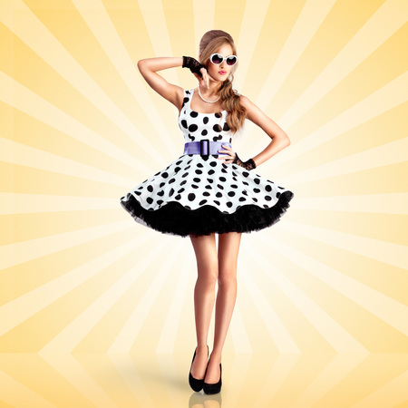 hot woman: Creative photo of a vogue pin-up girl, dressed in a retro polka-dot dress and sunglasses, posing on colorful abstract cartoon style background. Stock Photo