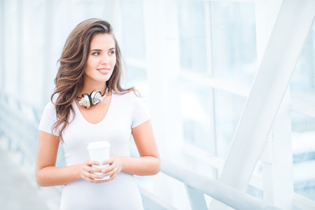 tea hot drink: Happy young woman wearing music headphones, standing on the bridge with a take away coffee cup and looking aside against urban background.