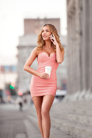 lady on phone: A pretty woman in a pink dress using mobile phone and holding a take away coffee. Stock Photo