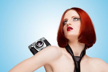 Glamorous girl, vamp style, wearing a necktie, holding an old vintage photo camera on her pretty shoulder on blue background.