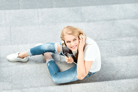 shopper: Top view of a beautiful young woman, listening to the music in music headphones, surfing internet on tablet and sitting on stairs. Stock Photo