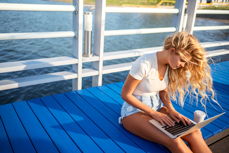 Beautiful young woman with a cup of take away coffee cup surfing internet via laptop.