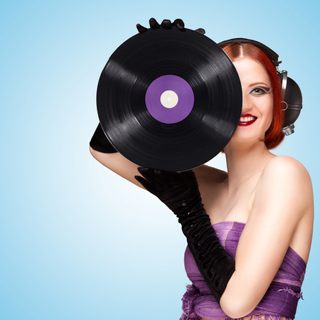 Colorful photo of a beautiful sexy girl wearing big vintage music headphones and holding a purple LP microgroove vinyl record in her hands on blue background. Stock Photo