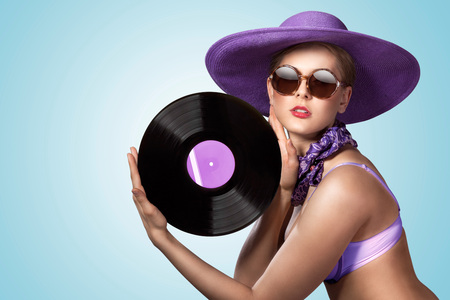 A photo of hot pin-up girl in vintage hat holding a vinyl records  LP. Stock Photo