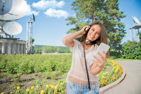 Beautiful young woman with vintage music headphones around her neck, surfing internet on a smartphone and standing against background of satellite dishes that receives wireless signals from satellites.