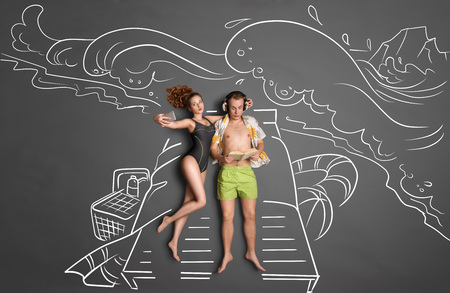 Love story concept of a romantic couple against chalk drawings background. Male lying on sun lounger, wearing headphones and reading a book, female taking selfie with a smartphone.