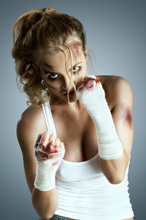 Aggressive female fighter with bruises wearing bloody bandage on her fists, standing in boxing defense position, ready to fight on a neutral grey studio background.