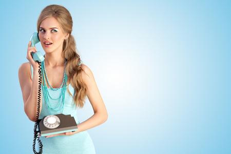 青の背景にビンテージ携帯電話を介して話すかなりピンナップ ガールの創造的な写真。