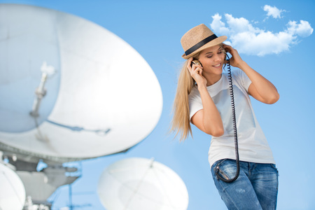 antena parabolica: Happy young woman in hat listening to the music in vintage music headphones and dancing against background of satellite dish that receives wireless signals from satellites.