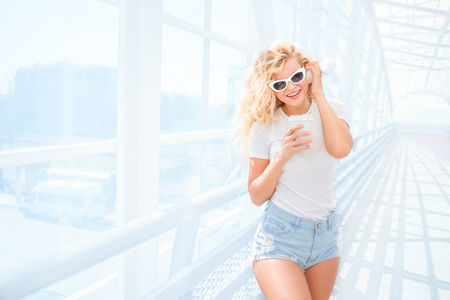 Beautiful young woman in sunglasses with music headphones, standing on the bridge with a take away coffee cup and smiling.