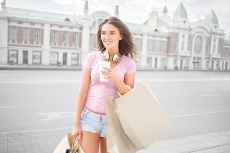 Beautiful young trendy woman wearing music headphones around her neck, drinking take away coffee and walking with shopping bags in an urban city. Stock Photo