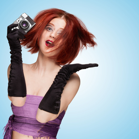 Glamorous emotional girl, wearing long gloves and disheveled hairstyle, holding an old vintage photo camera and jumping on blue background. Imagens