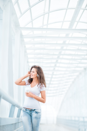 music background: Happy young woman wearing music headphones, standing on the bridge with a take away coffee cup and looking aside against urban background.