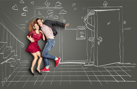 Happy valentines love story concept of a romantic couple sharing headphones and listening to the music on the stairs too loud for neighbors, against chalk drawings background. Stock Photo
