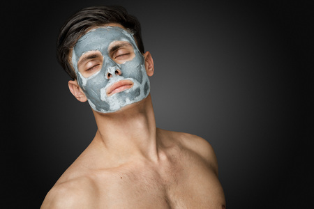 salon and spa: Portrait of a beautiful young man with a facial clay mask, face and body skin care treatment. Stock Photo