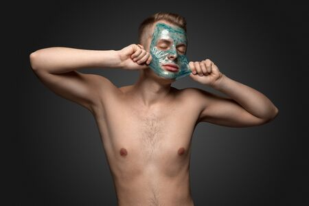 healthy body: Portrait of a beautiful young man peeling off a facial mask, face and body skin care retreat.