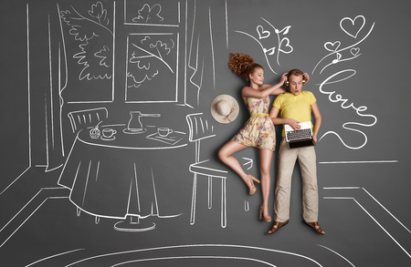 dinner date: Love story concept of a romantic couple against chalk drawings background. Male listening to the music in the headphones and surfing internet via laptop, female trying to gain his attention. Stock Photo