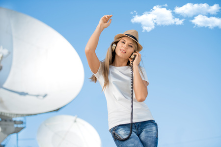 music background: Happy young woman in hat listening to the music in vintage music headphones and dancing against background of satellite dish that receives wireless signals from satellites.