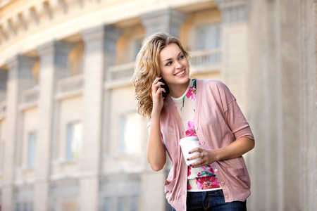 A beautiful woman chatting via phone and holding a cup of take away coffee.