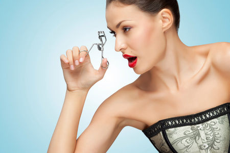 A pretty young woman holding an eyelash curler in her hand.