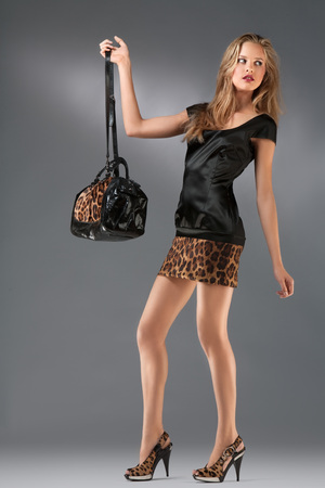 A studio portrait of a sexy hot lady in leopard clothes holding a bag. Stok Fotoğraf