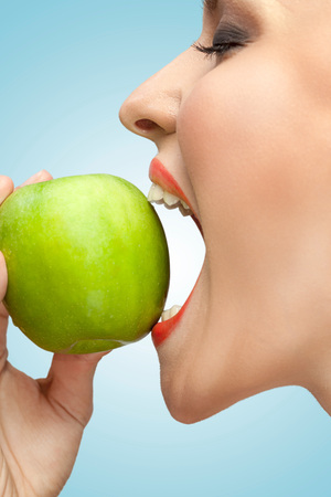 A portrait of a woman biting a green apple with her mouth wide open. Stock Photo