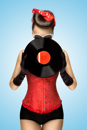 Vintage photo of a retro pinup girl, dressed in a red sexy corset, hiding behind retro vinyl on blue background.