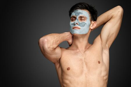 Portrait of a beautiful relaxed young man with a facial mud clay mask, face and body skin care treatment. Stock Photo