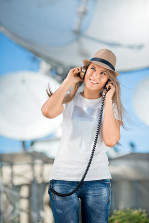 dish disk: Happy young woman in hat listening to the music in vintage music headphones and dancing against background of satellite dishes that receive wireless signals from satellites. Stock Photo