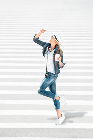 Beautiful young woman in a hat and jeans jacket with a takeaway coffee cup, standing on the road with zebra crossing, drinking coffee, and posing against road background.