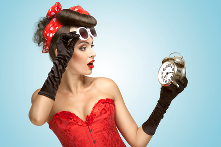 female sexuality: The conceptual photo of a pin-up girl in glamour underwear and gloves watching at the clock. Stock Photo
