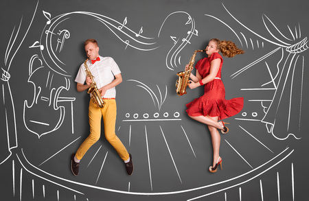 Love story concept of a romantic couple against chalk drawings background. Musician couple playing serenade on saxophone on stage.
