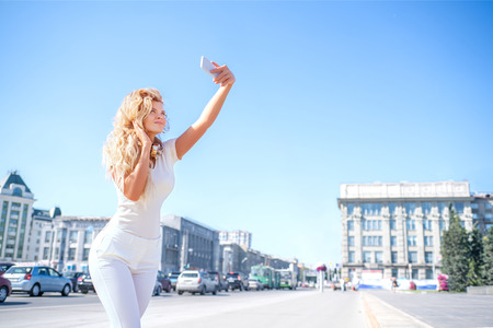 mobile: Beautiful young woman with music headphones around her neck, taking picture of herself, selfie against urban city background.