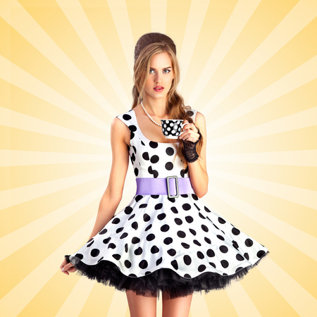 Creative vintage photo of a beautiful pin-up girl in a polka dot dress, holding a cup of tea on colorful abstract cartoon style background. Stock Photo